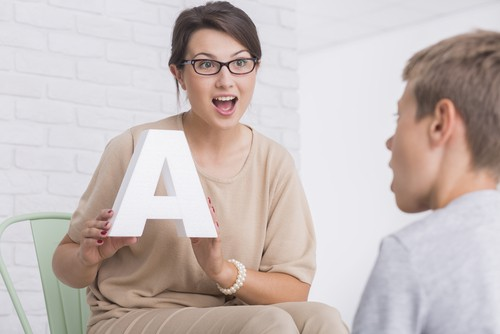 language tutor holds up letter A